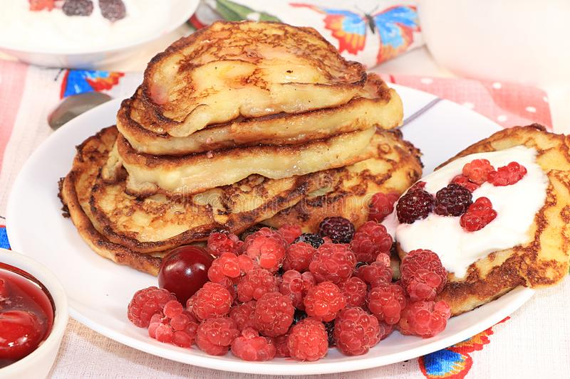 Delicious russian pancakes with cherries and raspberries and a mug of milk on a bright table, selective focus. Traditional Russian. Pancakes, natural food, jam stock images