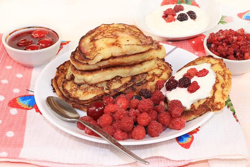 Delicious russian pancakes with cherries and raspberries and a mug of milk on a bright table, selective focus. Traditional Russian. Pancakes, natural food, jam royalty free stock image