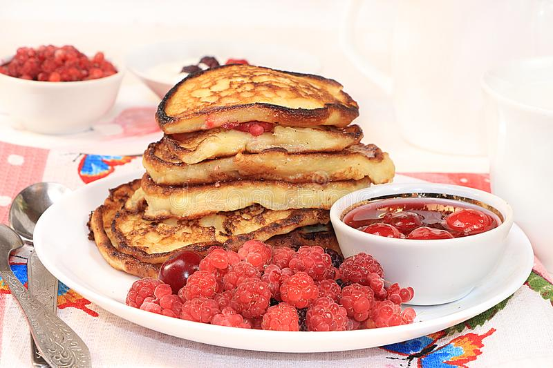 Delicious russian pancakes with cherries and raspberries and a mug of milk on a bright table, selective focus. Traditional Russian. Pancakes, natural food, jam stock photo