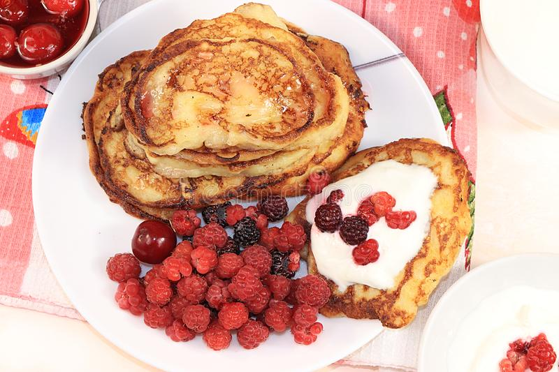 Delicious russian pancakes with cherries and raspberries and a mug of milk on a bright table, top view, flat lay, selective focus. Traditional Russian pancakes stock photography