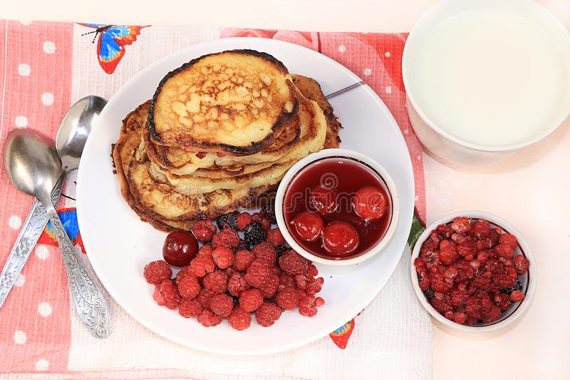 Delicious russian pancakes with cherries and raspberries and a mug of milk on a bright table, top view, flat lay, selective focus. Traditional Russian pancakes stock photos