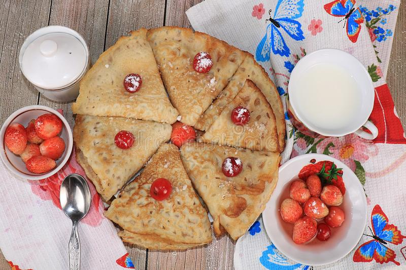Delicious Russian pancakes with cherries and strawberries and a mug of milk on a bright table, top view, selective focus. royalty free stock image