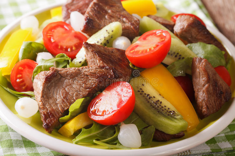 Delicious Salad with beef, kiwi, tomatoes, pepper and herbs close-up. horizontal. Delicious Salad with beef, kiwi, tomatoes, pepper and herbs in a bowl close-up royalty free stock photos