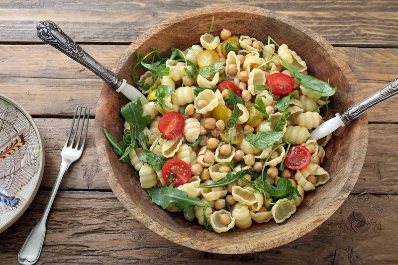 Delicious salad with boiled chickpeas pasta and tomatoes stock photo
