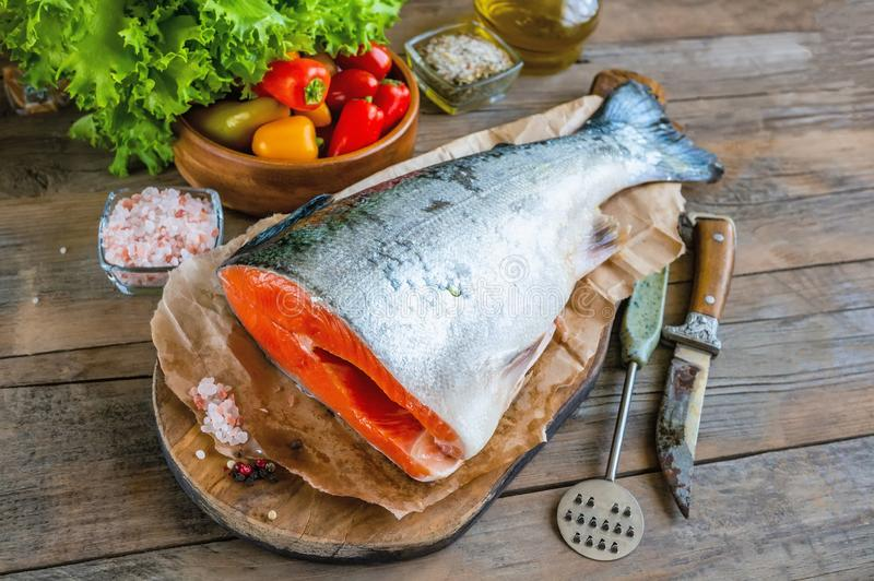 Delicious salmon fillet, rich in omega-3 oil, aromatic spices vegetables and lemon on fresh lettuce leaves on wooden background. stock images