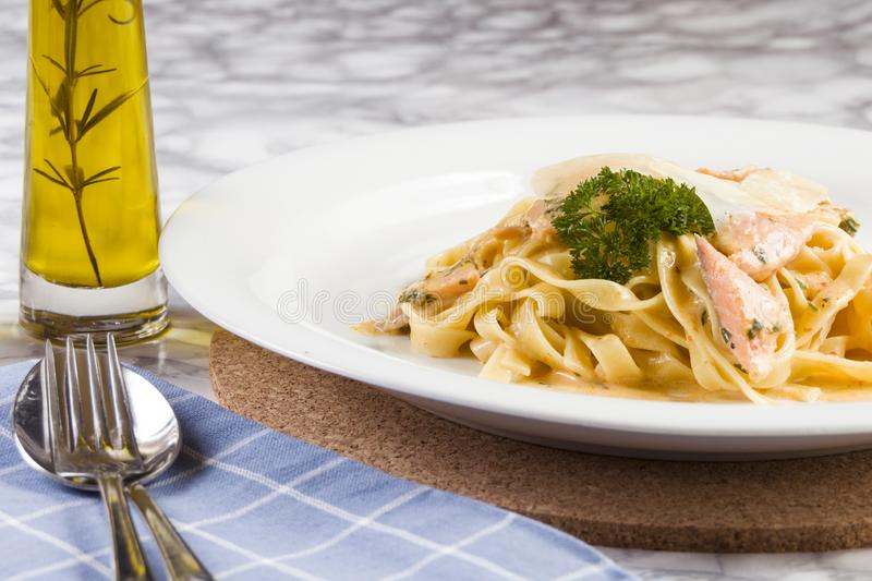 Delicious salmon pasta dish, tagliatelle noodles with Parmesan and parsley royalty free stock photo