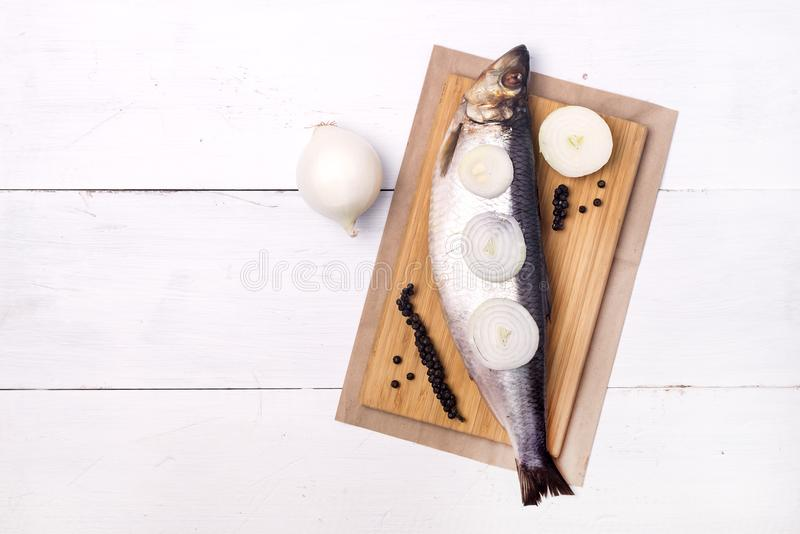 Delicious Salted Herring with Onion and Pepper on the Wooden Desk White Wooden Background Rustic Style Top View Copy Space royalty free stock photo