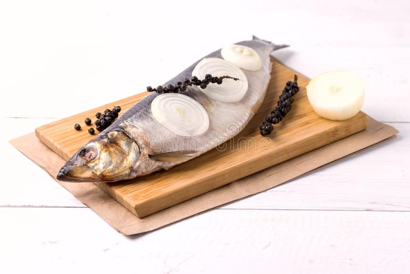 Delicious Salted Herring with Onion and Pepper on the Wooden Desk White Wooden Background Rustic Style Close Up royalty free stock photo