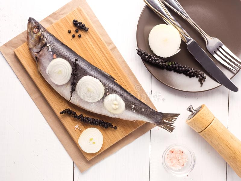 Delicious Salted Herring with Onion and Pepper on the Wooden Desk White Wooden Background Rustic Style Top View stock photo