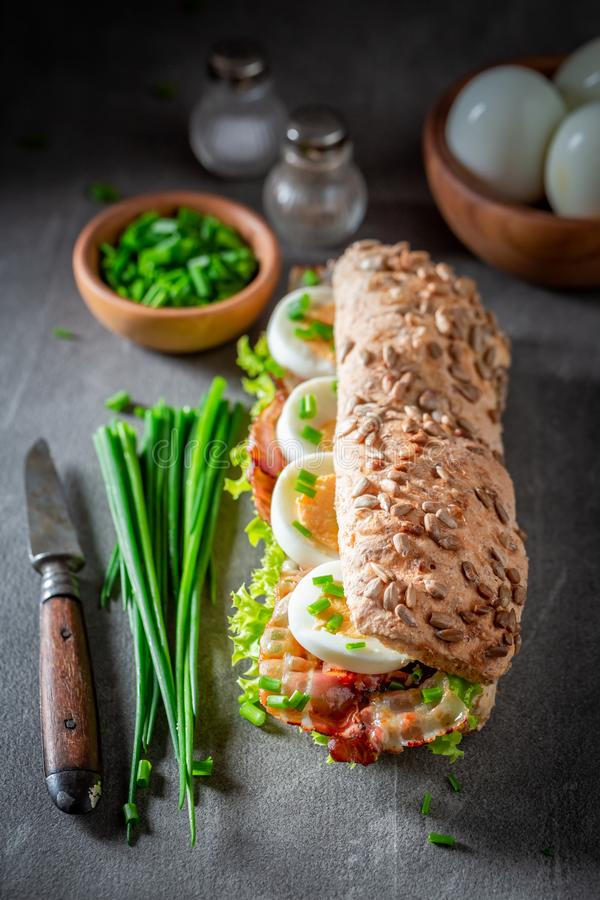 Delicious sandwich with bacon, chive and eggs. On grey table stock photo