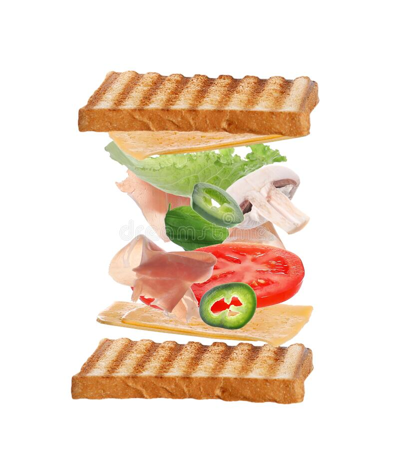 Delicious sandwich with flying toasted bread, prosciutto and other ingredients on background royalty free stock photos