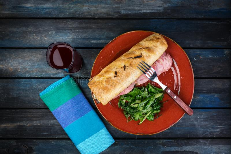 Delicious sandwich with fruit-drink ham mushrooms and green salad on a ceramic plate. Colored wooden background. Top stock image