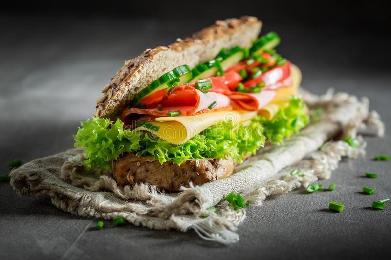 Delicious sandwich with ham, lettue and chive for breakfast. On grey table stock photos