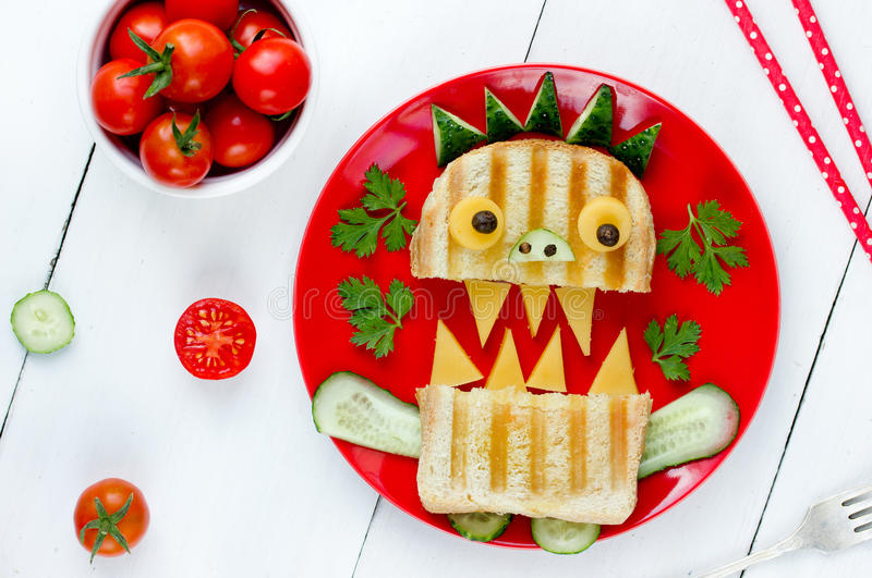 Delicious sandwich like a monster for kids party. Fun school lunch idea - toast with vegetables and cheese. Top view royalty free stock photos
