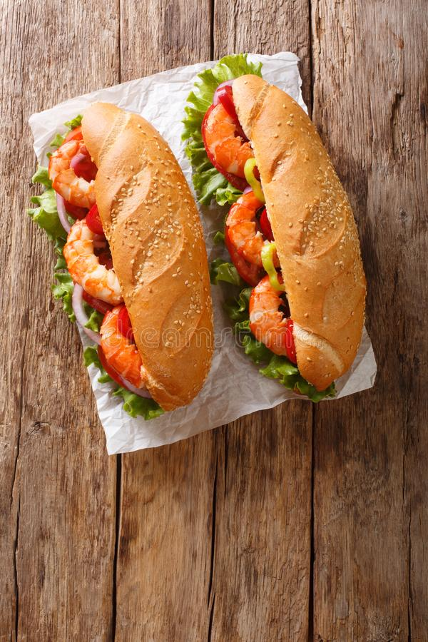 Delicious Sandwich with shrimps and fresh vegetables close-up on parchment. Vertical top view. Delicious Sandwich with shrimps and fresh vegetables close-up on royalty free stock image