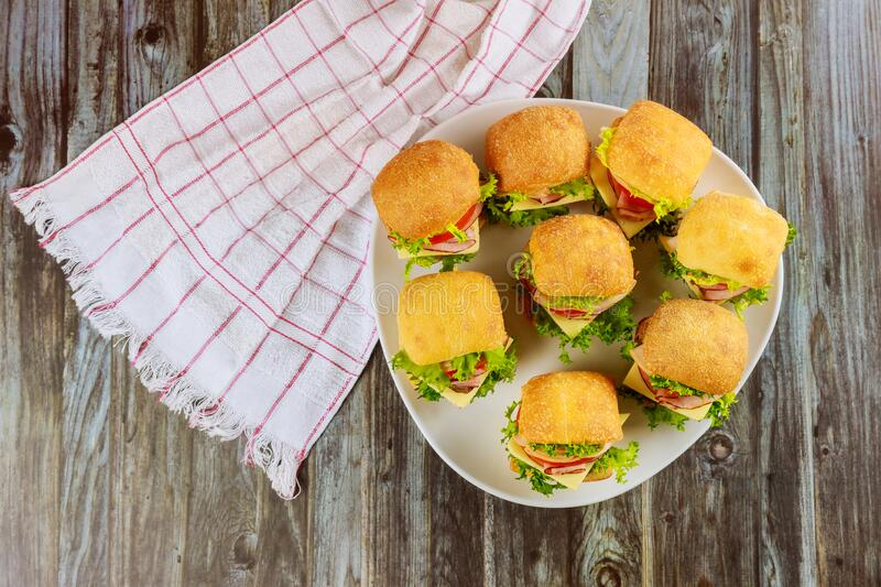 Delicious sandwiches on white plate on wooden background stock photos