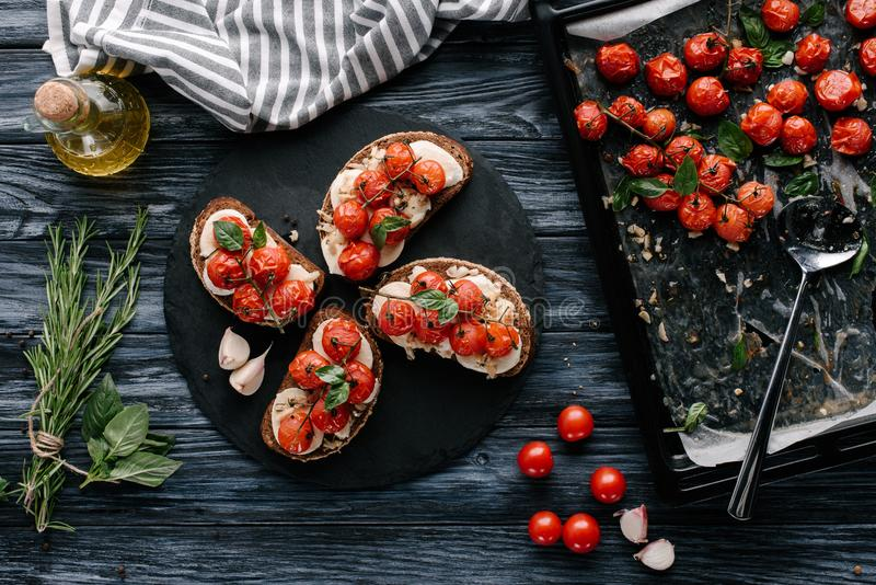 Delicious sandwiches with mozzarella and baked tomatoes on dark. Slate board stock photo