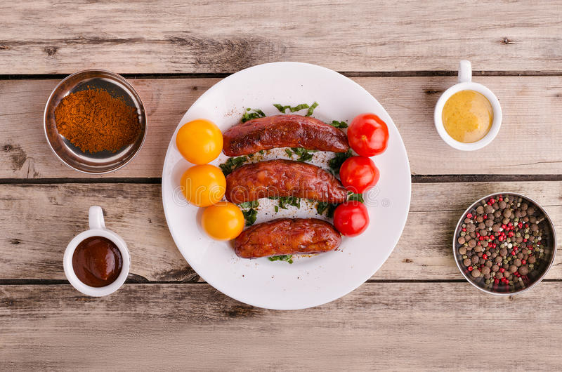 Delicious sausages. Sausage. Delicious sausages in a plate with ingredients. Salad. Spices. Vegetables royalty free stock photography