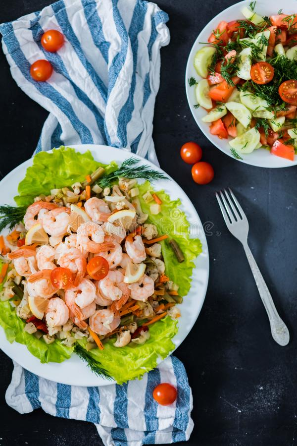 Delicious sauteed shrimp with cajun seasoning and lime on a maple plank white plate with salad and herbs on a black background,. Top view, closeup. Fresh stock image