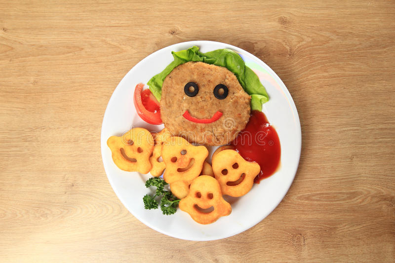 Delicious schnitzel and garnish on a dish in a children's restau. Rant royalty free stock photography