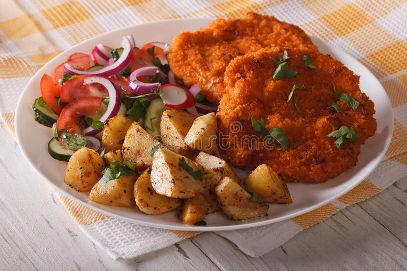 Delicious schnitzel, potatoes and vegetable salad closeup. horiz. Delicious schnitzel, fried potatoes and vegetable salad on the table close-up. horizontal stock image