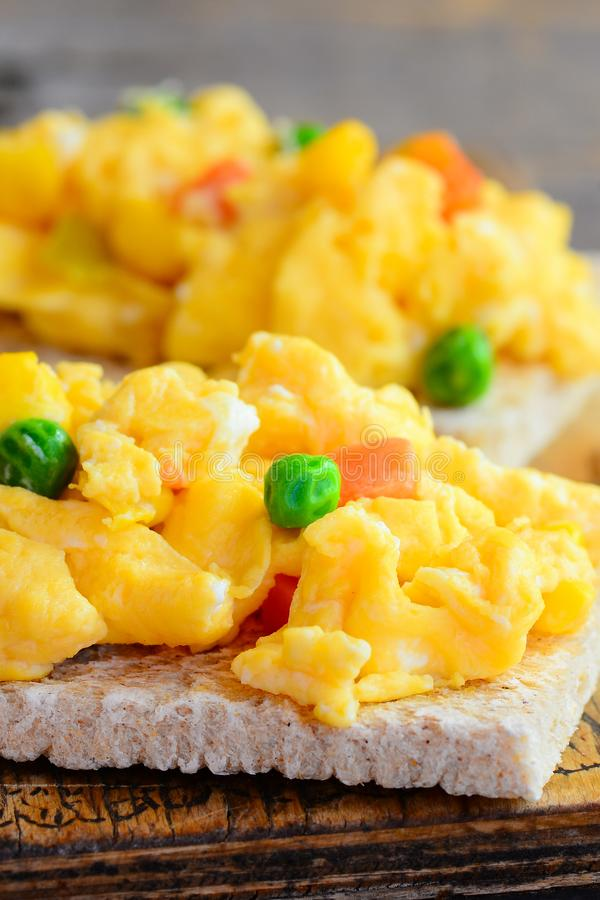 Delicious scrambled eggs with vegetables on crispy toast. Scrambled omelette toast recipe. Simple homemade cooking. Vertical photo stock images