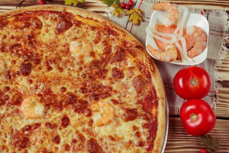 Delicious seafood italian pizza served on wooden table. stock photography