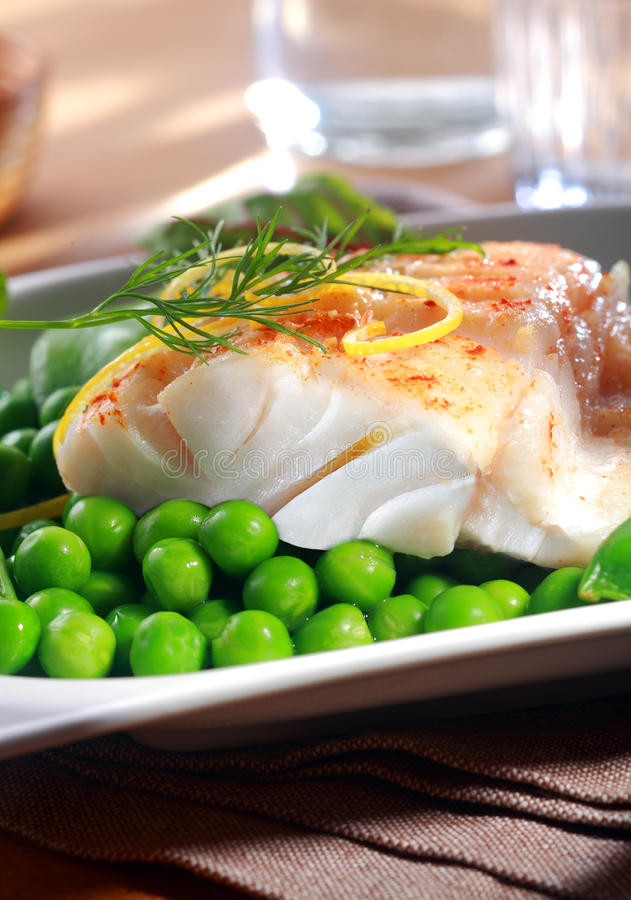 Delicious seafood meal of grilled fish. Delicious seafood meal of grilled or oven-baked fish fillet served with juicy green petit pois peas , lemon zest and dill stock photos