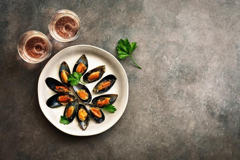 Delicious seafood mussels with spices, parsley and two glasses of pink sparkling wine, dark rustic background. Top view, flat lay stock photography