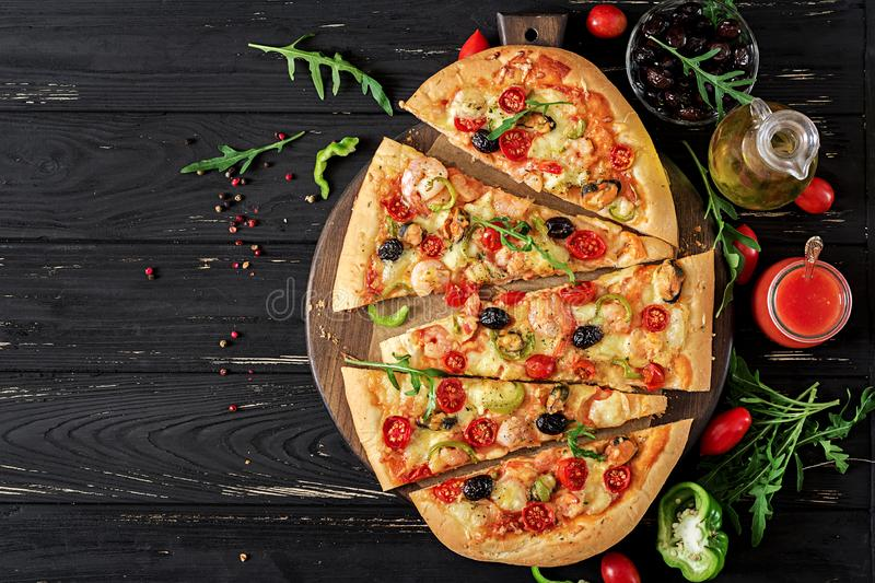 Delicious seafood shrimps and mussels pizza on a black wooden table. Italian food. stock images