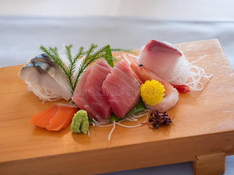 Japanese sashimi beautifully presented on a wooden board. A delicious set of Japanese sashimi laid out on a a wooden board stock image