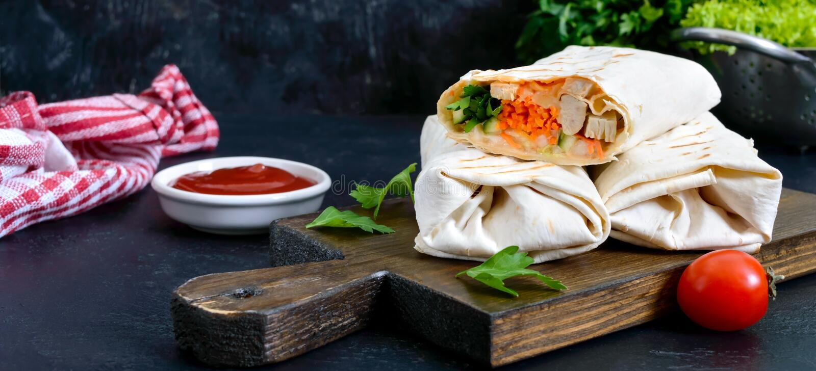Delicious shawarma sandwich on a black background. Burritos wraps with grilled chicken and vegetables, greens. stock photo