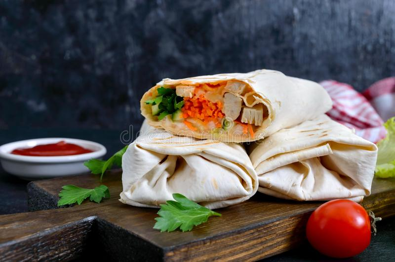Delicious shawarma sandwich on a black background. Burritos wraps with grilled chicken and vegetables, greens. stock photography