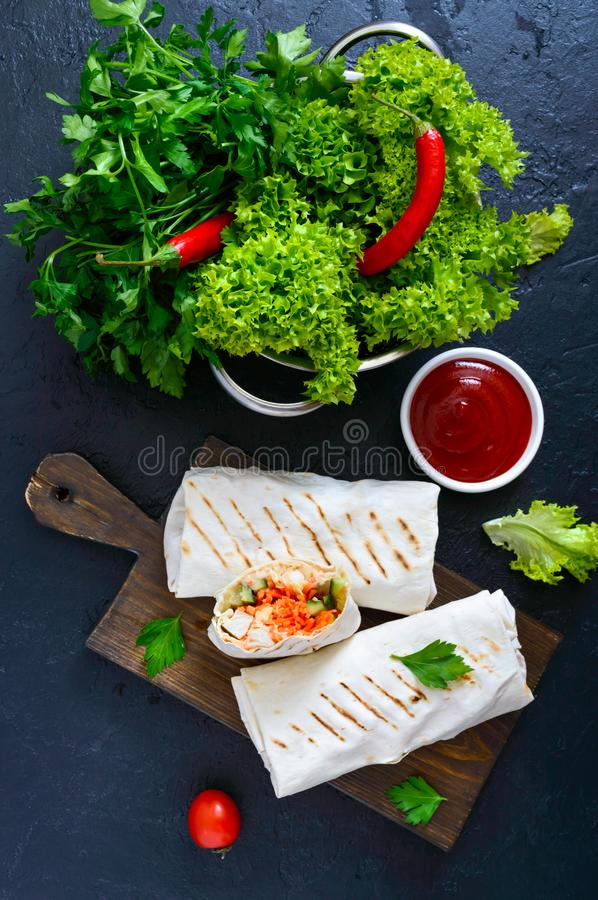 Delicious shawarma sandwich on a black background. Burritos wraps with grilled chicken and vegetables, greens. stock photos