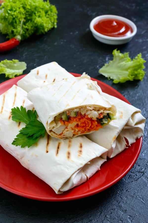 Delicious shawarma sandwich on a black background. Burritos wraps with grilled chicken and vegetables, greens. stock image