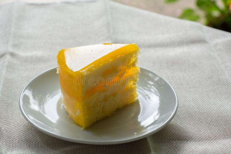 Delicious slice of orange cake. Served on white dish in coffee times on tablecloth stock photo