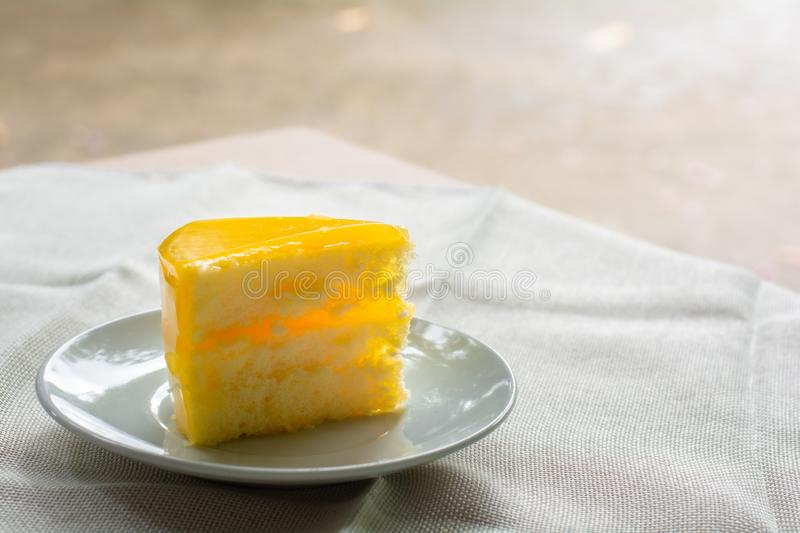 Delicious slice of orange cake served on white dish in coffee times on tablecloth.  royalty free stock image