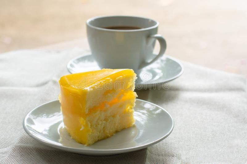 Delicious slice of orange cake served on white dish in coffee times on tablecloth. On wooden table royalty free stock photos
