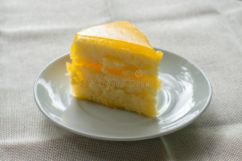 Delicious slice of orange cake served on white dish in coffee times on tablecloth. Bakery lover royalty free stock image