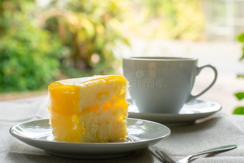 Delicious slice of orange cake served on white dish in coffee times on tablecloth. Bakery lover stock images