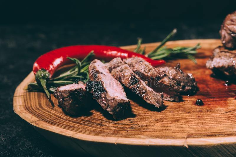 Delicious sliced grilled meat with rosemary and chili pepper on wooden board stock image