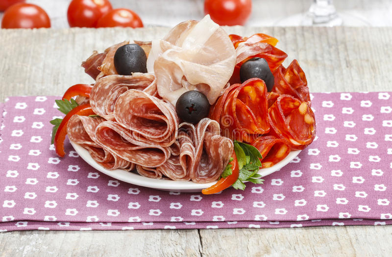 Delicious sliced ham. Platter of assorted cured meats and royalty free stock image