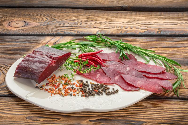 Delicious sliced pieces jerky lie on a wooden background, around the chilli pepper, herbs, spices stock image
