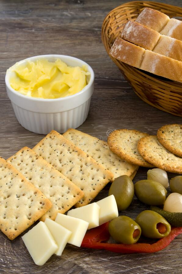 Delicious Snack, Crackers, Olives, Butter, Cheese and Bread in a Basket on Wood Table stock images