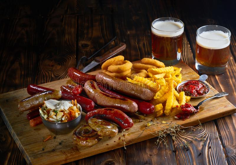 Delicious snacks with grilled sausages, fried potato, onion rings and two glasses of beer on wooden board in rustic royalty free stock photos