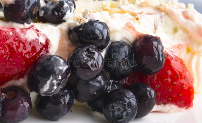 Biscuit cake with butter cream and fresh strawberries and blueberries royalty free stock image
