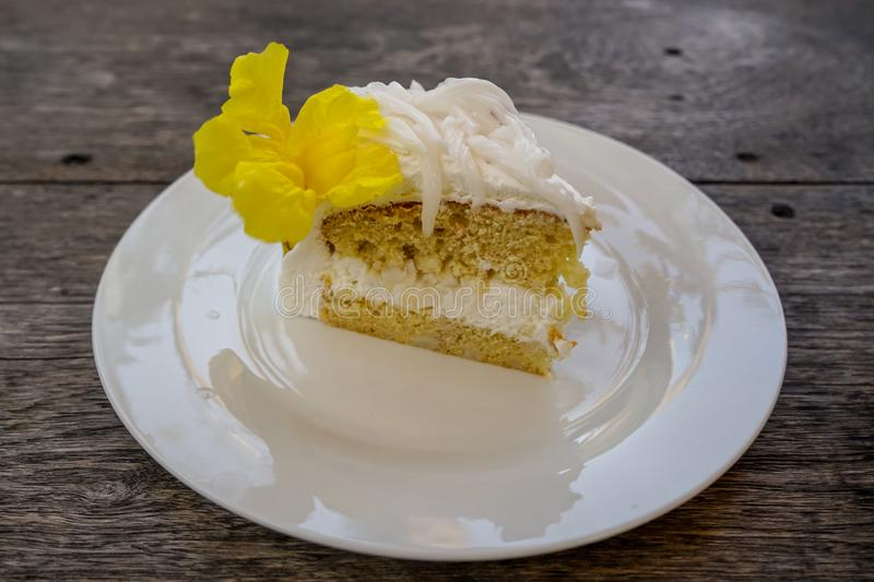 Delicious soft sweet white fresh coconut cake with beautiful yellow trumpet flower decoration on white ceramic plate on wooden stock photos