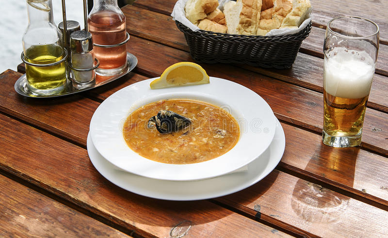 Delicious soup with shrimps, mussels, fish fillet and lemon. Delicious fish soup with shrimps, mussels, fish fillet and lemon. National cuisine of Montenegro royalty free stock photos