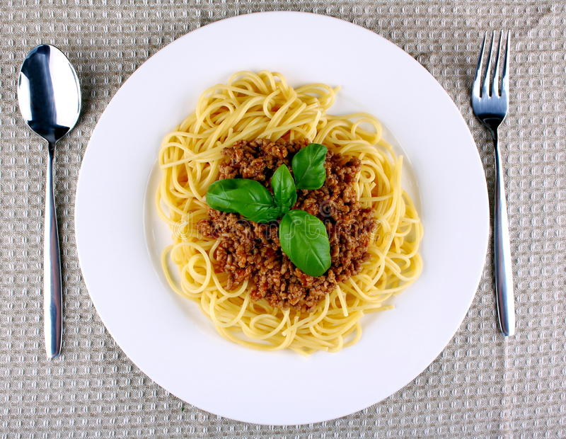 Delicious spaghetti bolognese with basil on white plate stock images