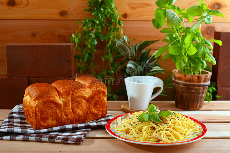 Delicious spaghetti with bread. On the dining table stock photos